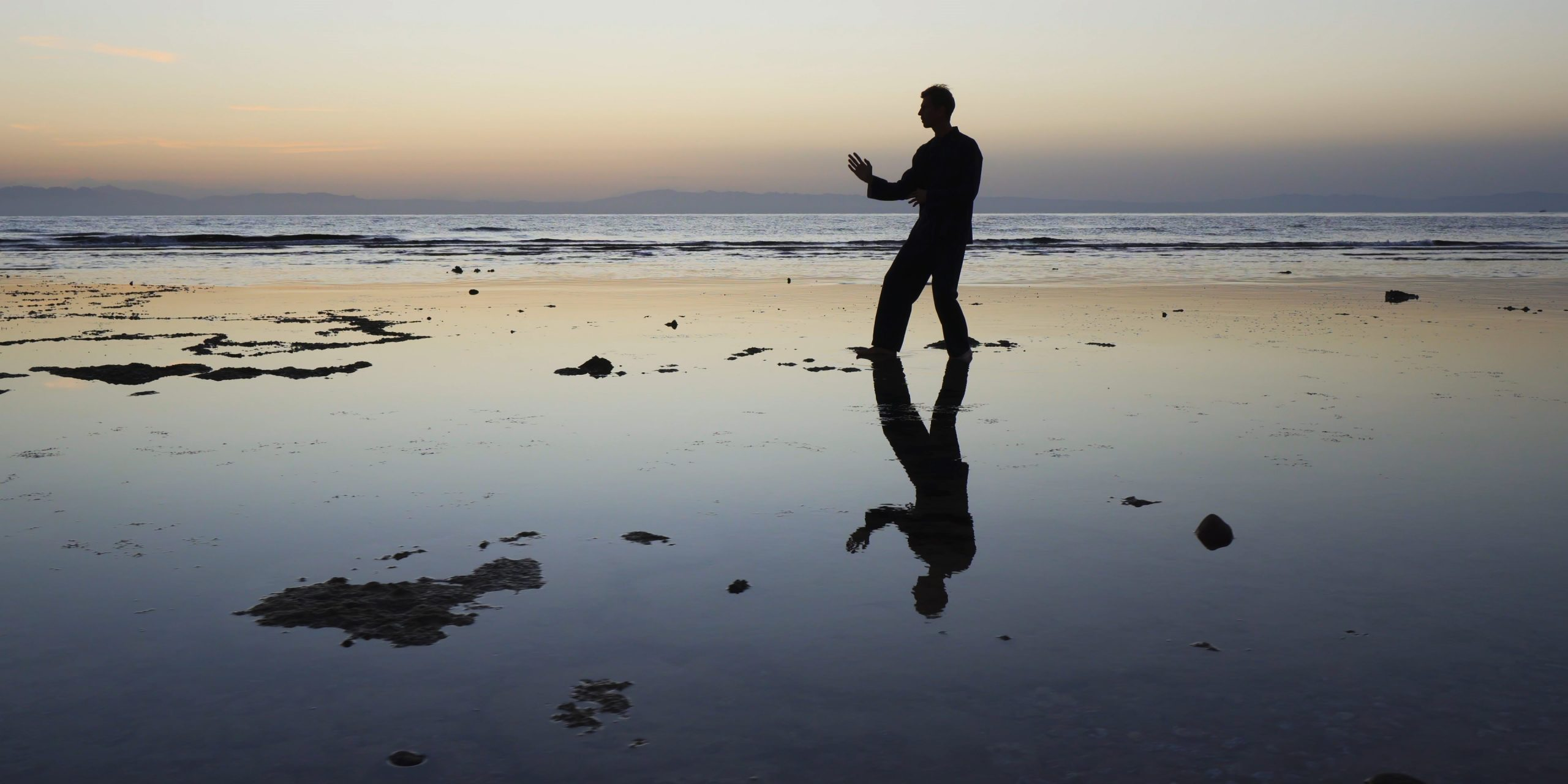 Silhouette of man practiceing qigong exercises at sunset by the sea.
